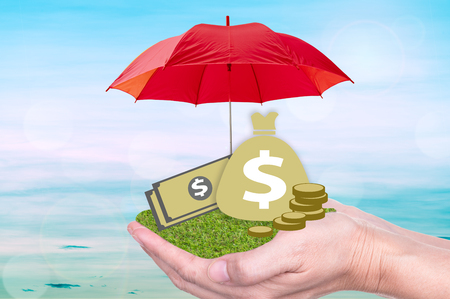 Deposit protection, protect investment or banking concept. money bag, banknote on hand with protected by umbrella.
