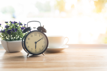 Alarm clock closeup have a good day with a cup of coffee and flower pots background in the morning sunlight. 写真素材