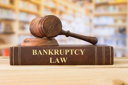 Książki z zakresu prawa upadłościowego z młotkiem sędziowskim na biurku w bibliotece. Pojęcie prawa upadłościowego, upadłość, sąd upadłościowy, edukacja prawnicza, książki prawnicze.