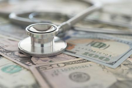 argent médical, stéthoscope sur billet de dollar. concept de frais médicaux, finances, assurance maladie.