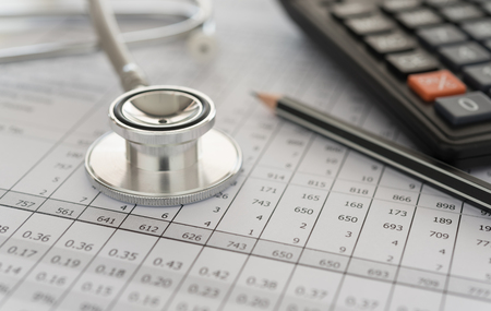 medical billing,  stethoscope and calculator on bills for health care costs or medical insurance.