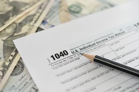 U.S. Individual Income Tax Return - 1040 tax form with pencil on dollar banknote. Concept of tax return, tax refund.