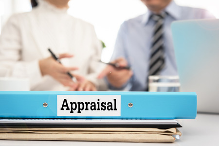 Los documentos de evaluación en el escritorio con el gerente y la junta se discuten sobre la evaluación de la propiedad o el proceso de evaluación y las calificaciones de desempeño.