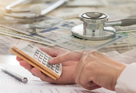 health care costs or health insurance funds concept. Stethoscope,money and women calculated health costs. Standard-Bild