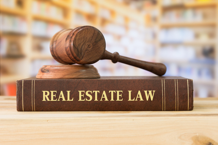 livres de droit immobilier et un marteau sur le bureau de la bibliothèque. concept de l'éducation juridique.