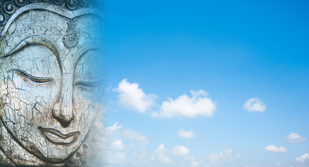 Buddha carved from wood on sky background. Stock Photo