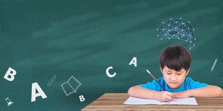 Education concept, Boy sitting with books on the table and Brain on green board background. With space for your message.