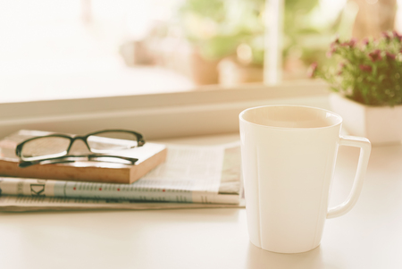 Morning coffee, Cup of coffee with newspapers, glasses, books and flower pots is placed near the window.