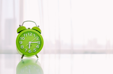 Green alarm clock on the table and white background.
