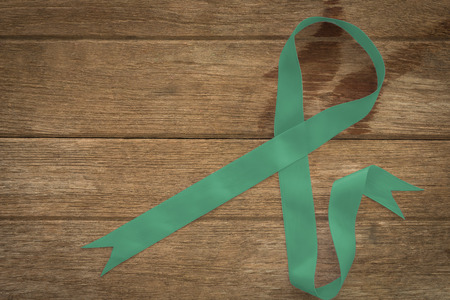 Ovarian cancer and gynecological disorders concept. Green ribbon symbolic support campaign on people living life with Ovarian cancer Stok Fotoğraf