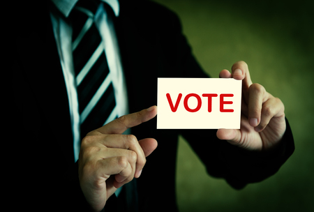 Businessman showing vote card in hand with a dark background. Stock Photo