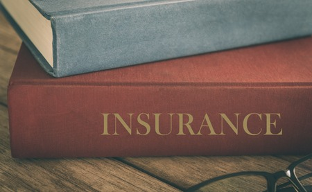 Learn insurance concept. Old law book on the topic of insurance on wood table. Standard-Bild - 116707156