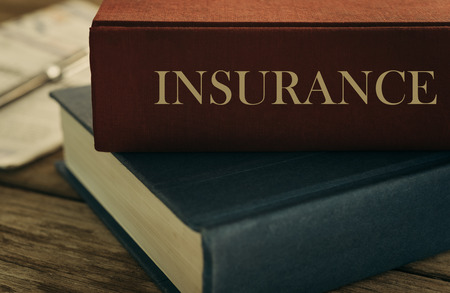 Learn insurance concept. Old law book on the topic of insurance on wood table.