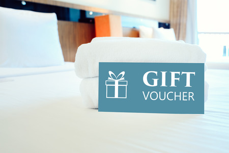 Gift voucher concept. Gift voucher card placed inside a hotel room bed with White towel. Standard-Bild - 116707365