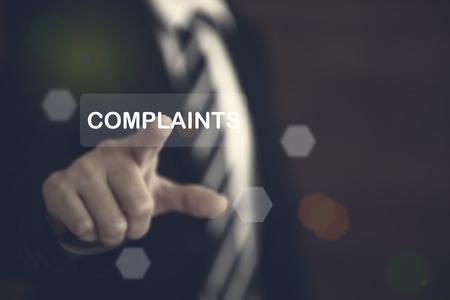"""Beschwerden Konzept. Geschäftsmann, der auf die Schaltfläche """"Beschwerden Text"""" auf virtuellen Bildschirmen zeigt."""