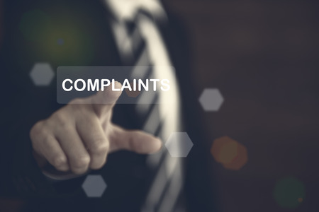 Complaints concept. Businessman pointing the text Complaints button on virtual screens.