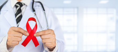 Doctor Holds Red Ribbon to awareness world aids day Dec. 1 Standard-Bild - 116707874