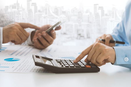 businessman using calculator with business report and marketing team brainstorming process to data analysis and new startup project. Standard-Bild - 119797764