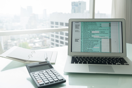 Individual income tax return forms online on screen laptop computer on desk of accountant. Standard-Bild - 119797800
