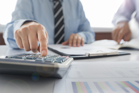 Businessman using a calculator to calculate the numbers. Accounting , Accountancy, Calculation Concept. Standard-Bild - 119798694