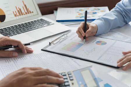 Het team van financiële adviseurs analyseert het rendement op de investering uit het rapport met bedrijfsgrafieken. Concept van financiële planning, boekhouding en data-analyse.