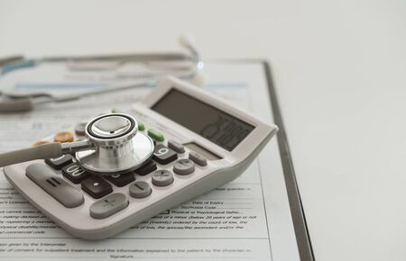 Medical expenses plan or health insurance. Stethoscope on calculator with medical bill.