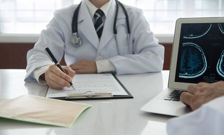 medical concept. doctor take notes on medical report with stethoscope on cardiogram chart on desk at doctor office.