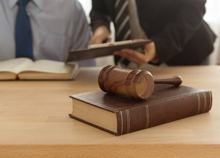 law,legal,legislation concept. judge hammer on legal book with lawyer and attorney consult in legal office.
