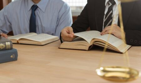 Lawyer or attorney team meeting and reading the legal books in law firm. Concepts of law, advice,legal services.