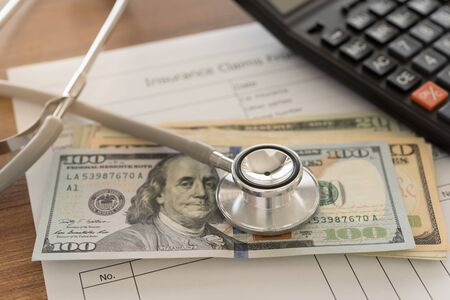 Health insurance claim concept. Stethoscope on money with calculator, health insurance claim form on desk.