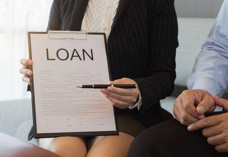 L'impiegato di banca ha consegnato la penna per firmare il documento di prestito e il contratto. Concetto di prestiti ipotecari.