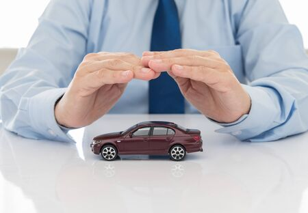 car insurance concept. businessman protection of car (automobile). Stockfoto