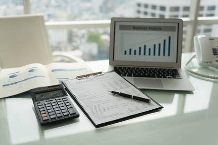 Werkplek. De pen op balansrapport met rekenmachine, laptopcomputer met bedrijfsgrafiek voor analyseprestaties van bewerking. Stockfoto