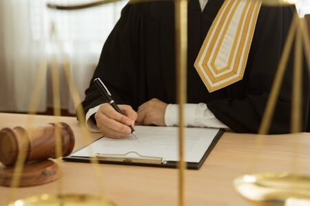 law and legislation concept. judge signing legal document in courtroom with scales of justice and judge gavel on desk.