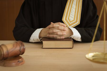 Attorney sitting in courtroom with law books, scales of justice and judge gavel on desk. law and legislation concept.