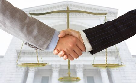 Lawyer shaking hands with businessman with court and scales of justice