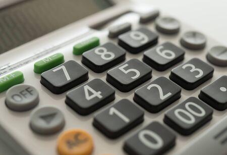 Calcolatrice del primo piano su bianco