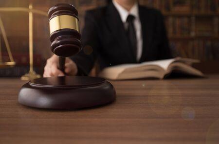 Mannelijke rechter werken met de houten hamer en schalen van Justitie op bureau in rechtszaal. Stockfoto