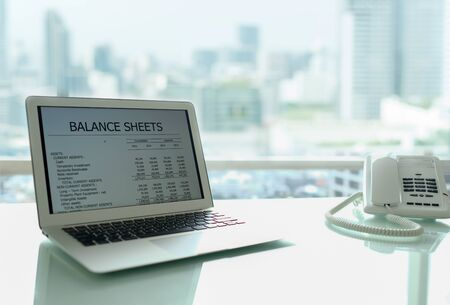 Accounting business concept. Balance sheet and business earning report showing on laptop computer screen.