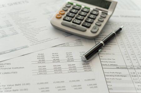 Pen, calculator, financial statement on accountants desk.