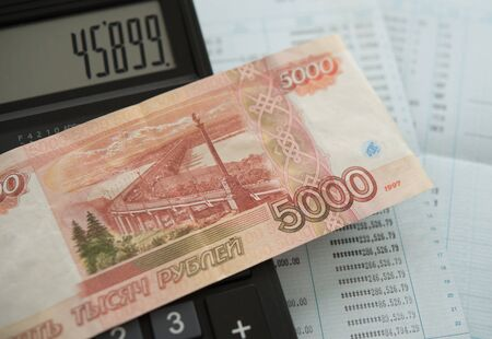 Russian ruble money on bank account passbook with calculator on desk.