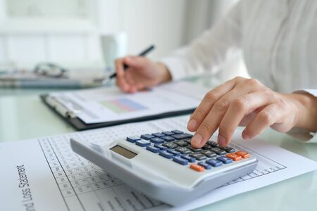 Financial advisor calculating and analyzing for performance business assessment.