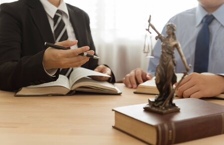 Lady justice on law book with lawyer team meeting in law office.