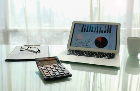 Calculator with financial graph spreadsheet on screen and business earning report on desk. Stock fotó