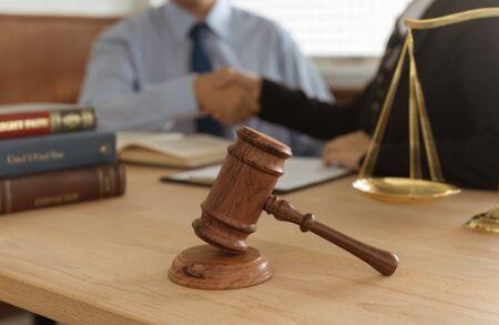 Juez martillo, balanza de justicia y libros de derecho y apretón de manos de abogado con cliente y asesoría legal. Foto de archivo