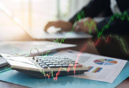 Calculator on business report with index stock market and uptrend line graph stock market with financial advisory planning and strategy in investing.