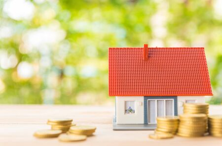 Savings for housing/ insurance and loans concept. House and pile of gold coins against a natural bokeh background.