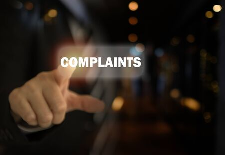 Businessman pointing the text Complaints button on virtual screens.