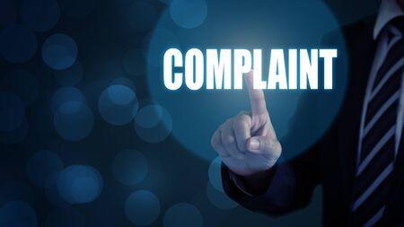 Businessman pointing the text Complaints button on virtual screens. Zdjęcie Seryjne