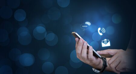 CONTACT US, Hand of a businessman holding a mobile smartphone with the icon.